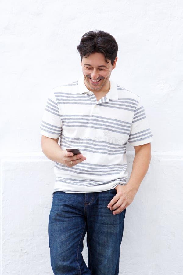 Mensagem de texto da leitura do homem mais idoso em seu telefone celular imagens de stock