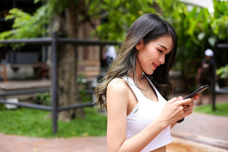Mensagem de texto de datilografia da jovem mulher do esporte da saúde no telefone esperto e fotos de stock