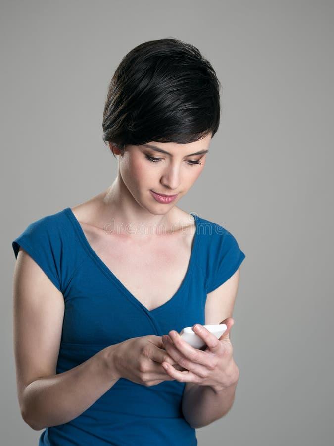 Mensagem de texto de datilografia da beleza ocasional nova do cabelo curto no telefone esperto foto de stock
