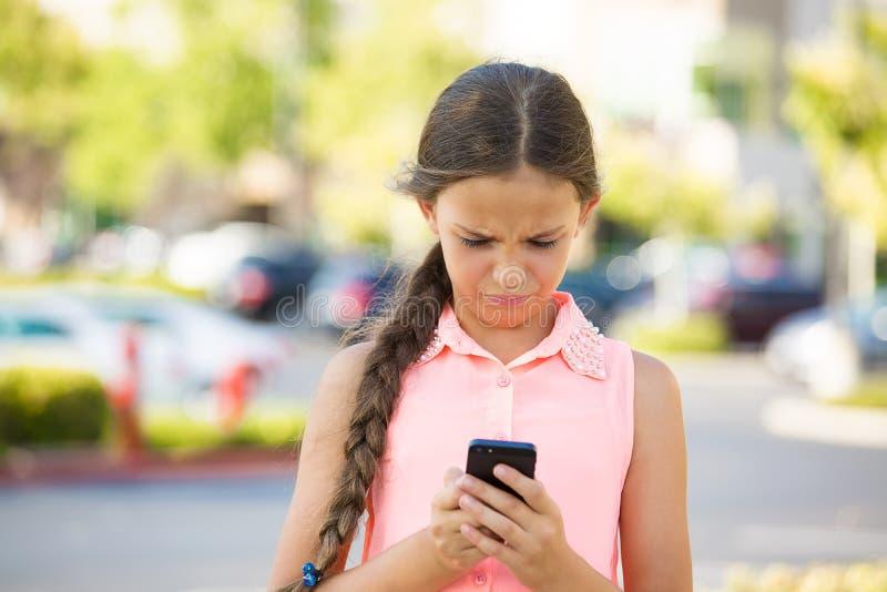 Mensagem de texto infeliz da leitura da menina no telefone esperto fotos de stock