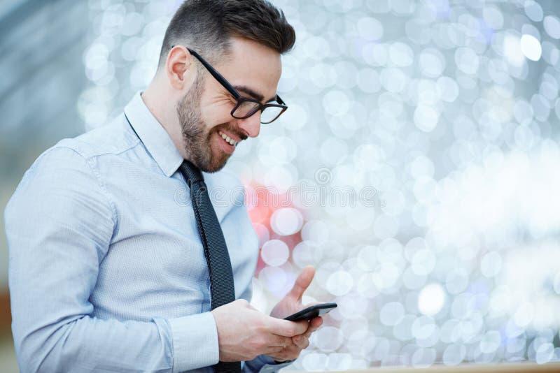 Mensagem de texto moderna de Reading do homem de negócios com boa notícia foto de stock royalty free