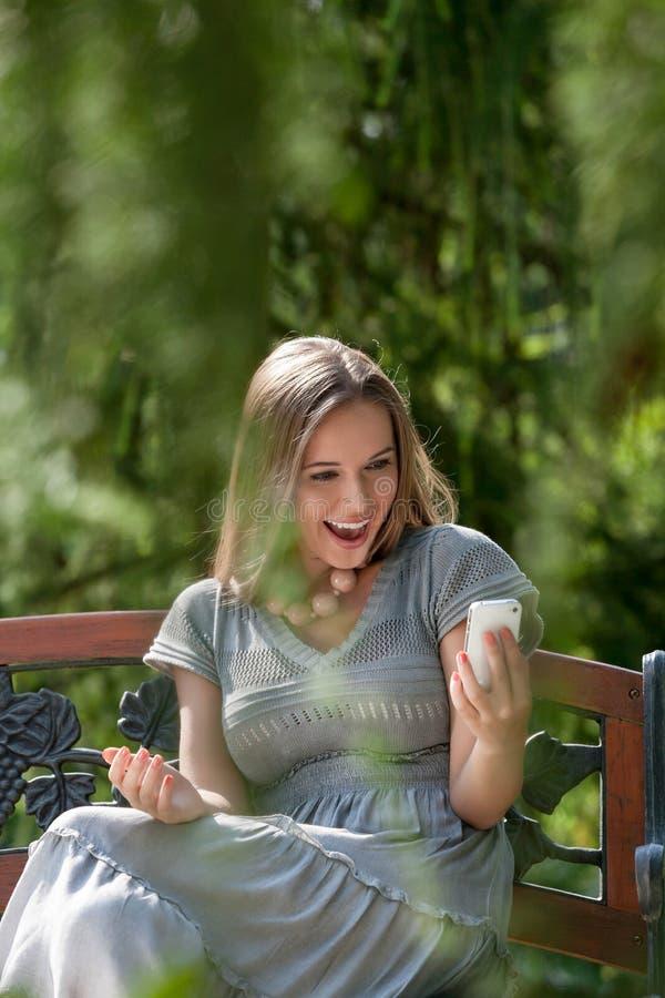 Mensagem de texto surpreendida da leitura da jovem mulher no telefone esperto no parque foto de stock royalty free