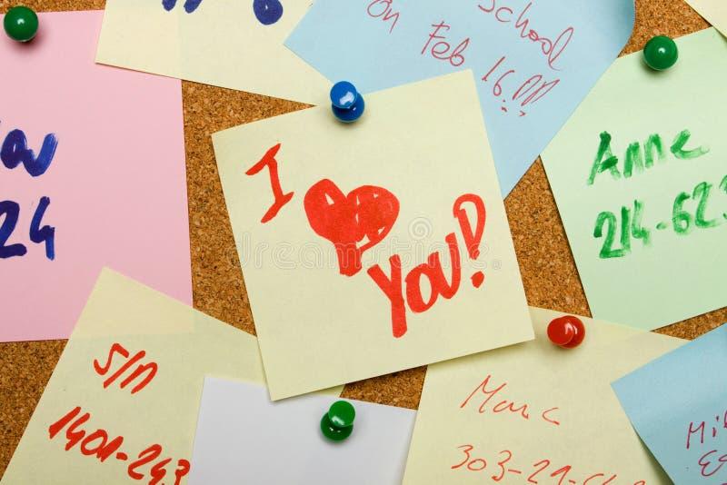 Mensagem do amor fixada na placa da cortiça imagem de stock