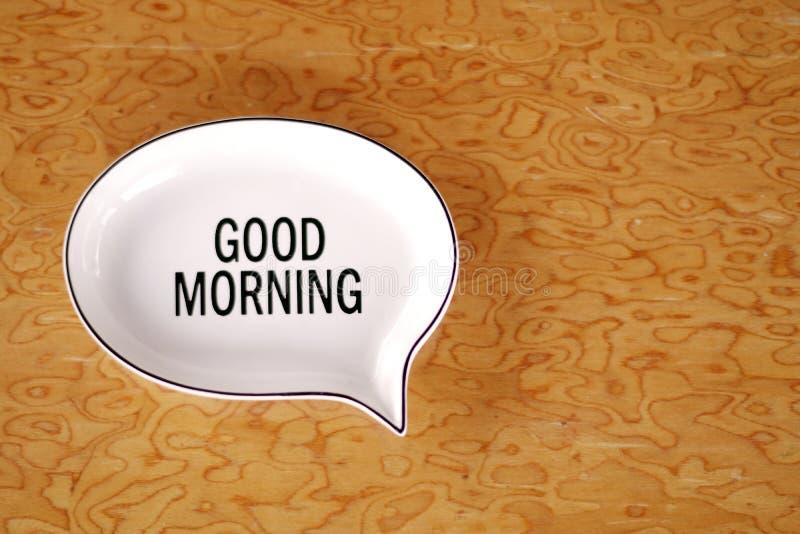 Mensagem do bom dia em uma placa branca da telha em um fundo de madeira imagens de stock