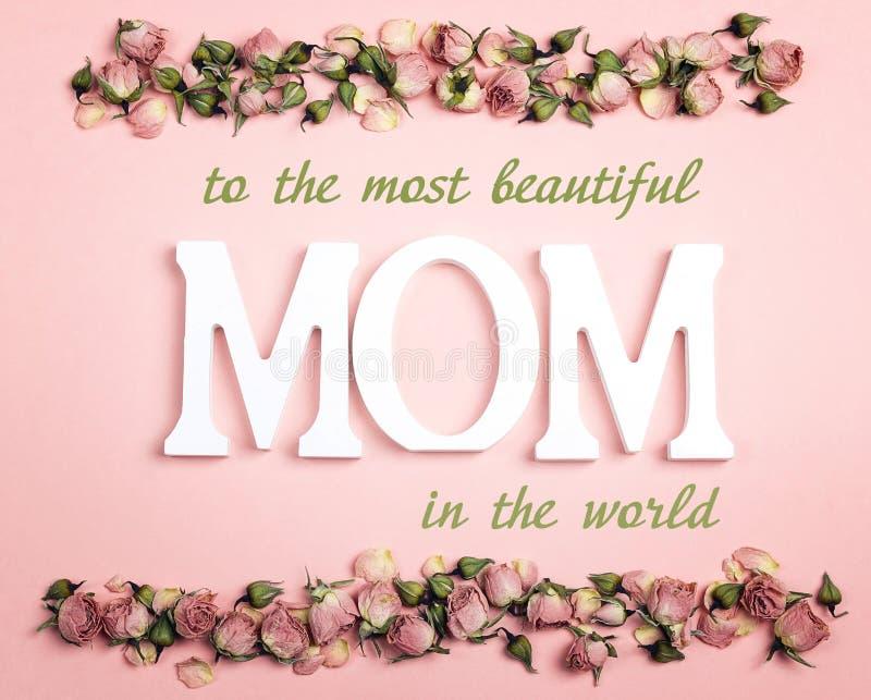 Mensagem do cumprimento do dia de mães com as rosas secas pequenas no backgr cor-de-rosa fotografia de stock royalty free