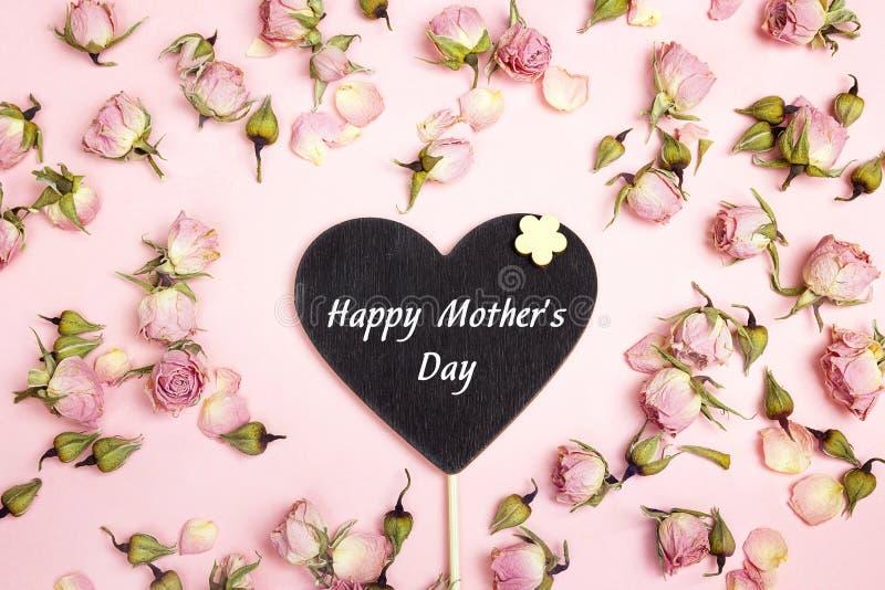 A mensagem do cumprimento do dia de mães no coração-quadro-negro com pequeno seca fotografia de stock royalty free