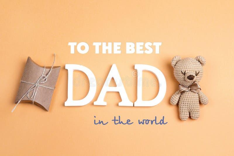 Mensagem do cumprimento do dia do ` s do pai com urso do brinquedo e caixa de presente no grito fotos de stock