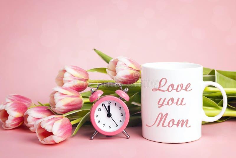 Mensagem do dia de mães na caneca de café branco com flores e despertador da tulipa no fundo cor-de-rosa fotos de stock royalty free