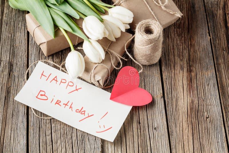 Mensagem do feliz aniversario com as flores na tabela rústica com flores foto de stock royalty free