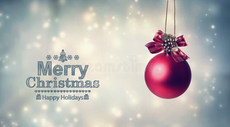 Mensagem do Feliz Natal com uma quinquilharia de suspensão fotografia de stock royalty free