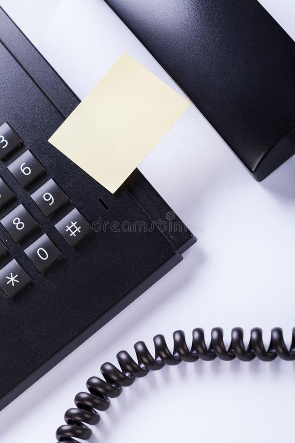 Mensagem do post-it do memorando no telefone no escritório foto de stock
