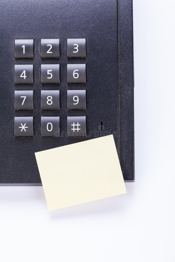 Mensagem do post-it do memorando no telefone no escritório fotografia de stock