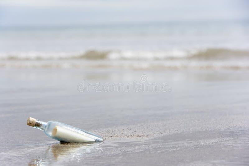 Mensagem em um frasco enterrado na areia foto de stock royalty free