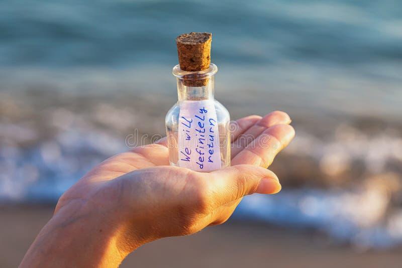 Mensagem em uma garrafa com a inscrição: nós retornaremos definidamente fotos de stock