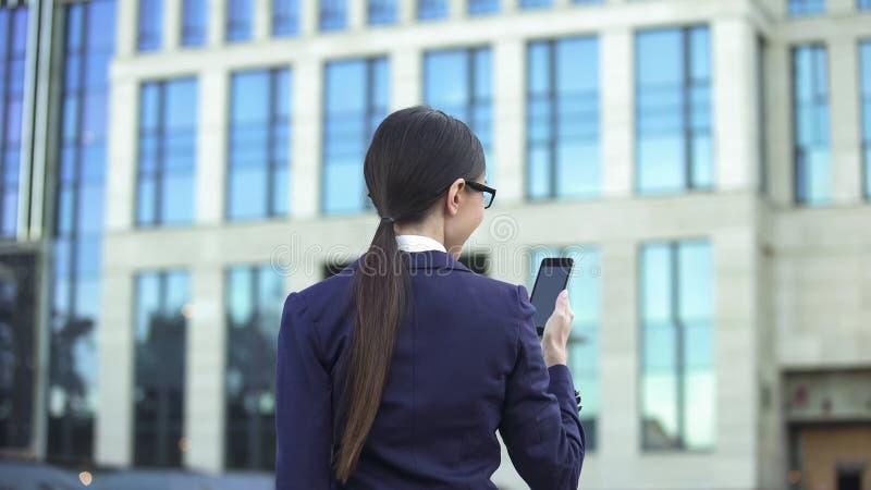 Mensagem fêmea no ar livre do smartphone, app social da leitura do trabalhador de escritório da rede imagem de stock