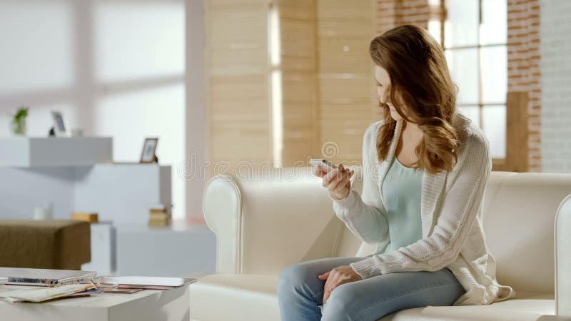Mensagem feliz da leitura da mulher com a boa notícia, satisfeita com o app no telefone celular imagem de stock royalty free