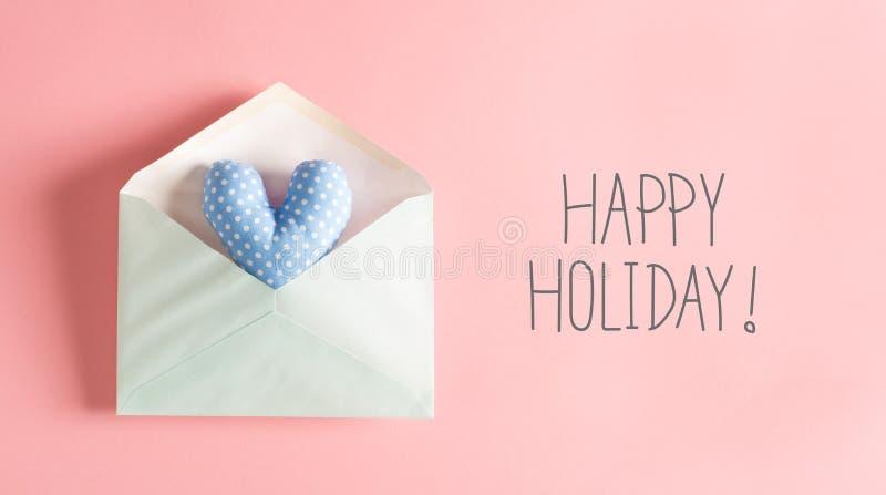 Mensagem feliz do feriado com um coxim azul do coração imagens de stock