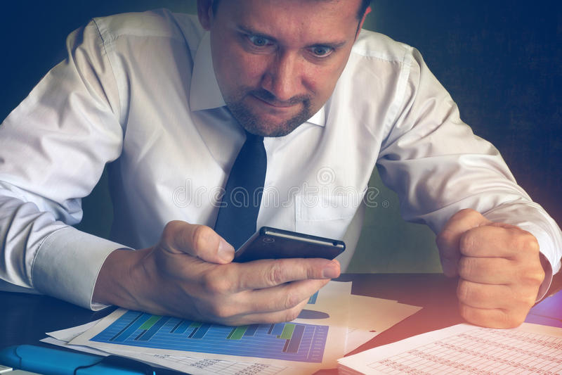 Mensagem irritada da leitura do homem de negócios em um smartphone foto de stock royalty free