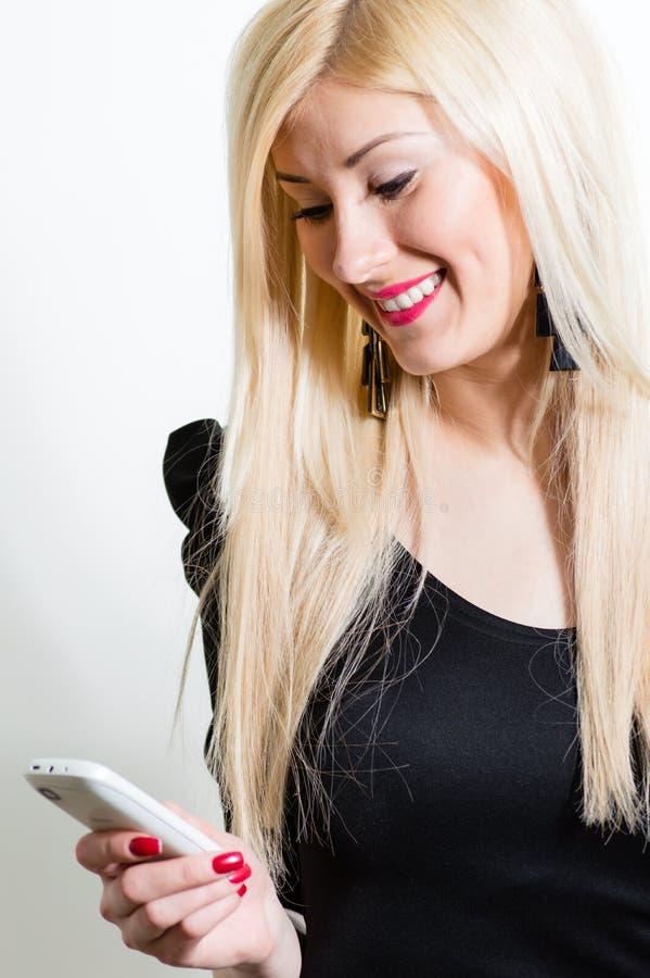 Mensagem loura de sorriso feliz bonita da leitura da jovem mulher no móbil foto de stock royalty free