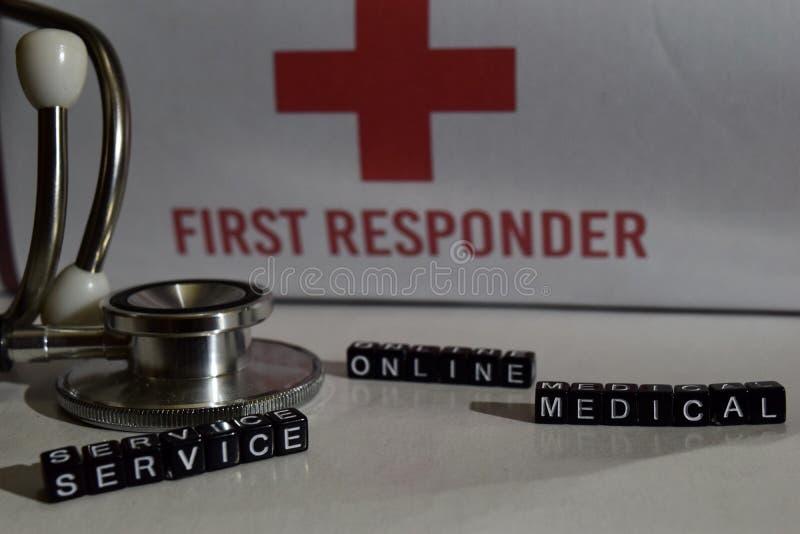 Mensagem médica do serviço online escrita em blocos de madeira Estetoscópio, conceito dos cuidados médicos imagens de stock royalty free