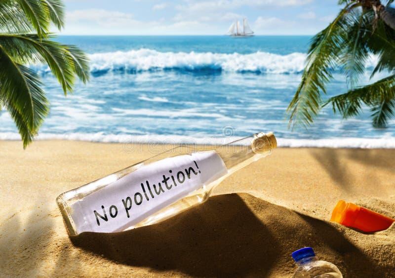 Mensagem na garrafa com a mensagem nenhuma poluição na praia foto de stock royalty free