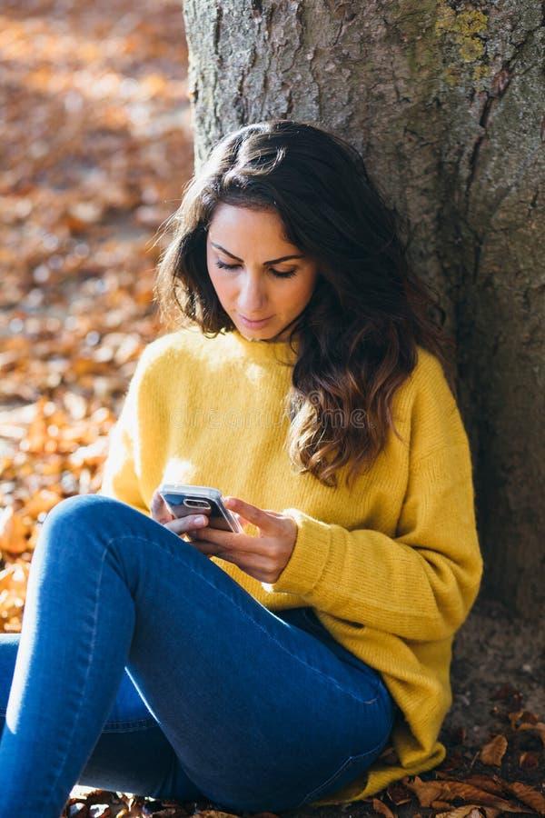 Mensagem ocasional da mulher no telefone esperto no outono fotografia de stock
