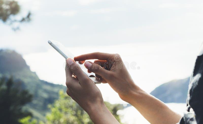 A mensagem texting da menina do moderno no fim do móbil do smartphone acima, turista da vista entrega usando o telefone do dispos imagem de stock
