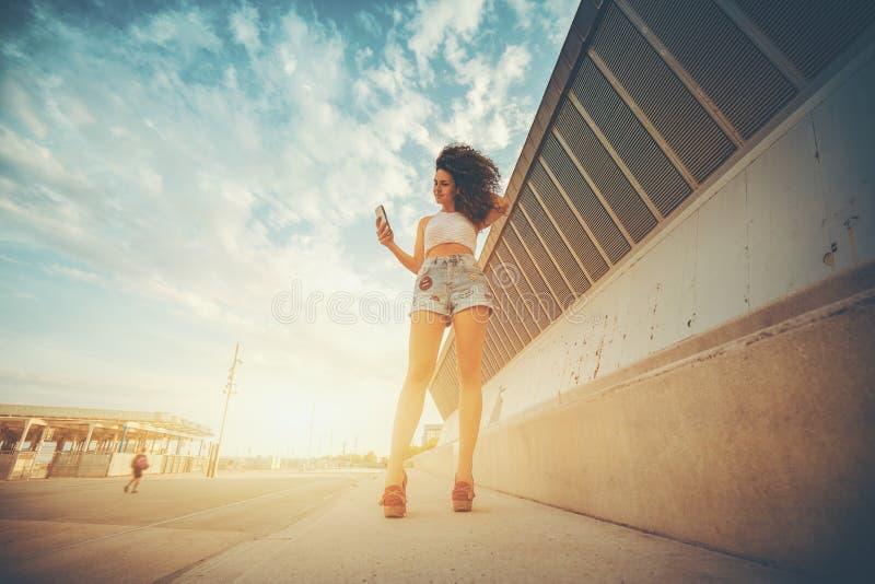 Mensagem texting da menina moreno encaracolado nova em seu telefone foto de stock