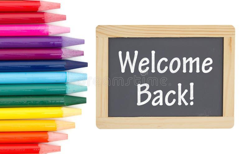 Mensagem traseira bem-vinda em um quadro com os lápis coloridos da aquarela foto de stock