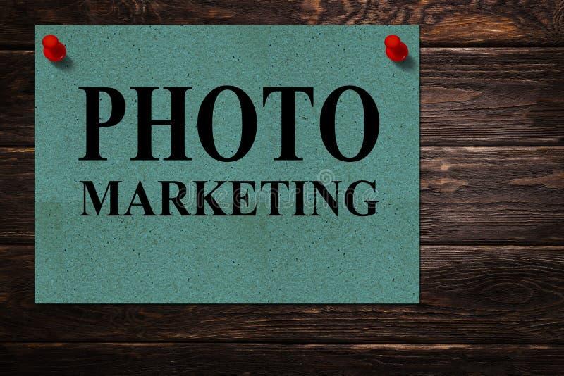 Mensagens 'MERCADO da FOTO 'escrito em suportes de papel verdes como uma propaganda em uma superfície de madeira imagens de stock