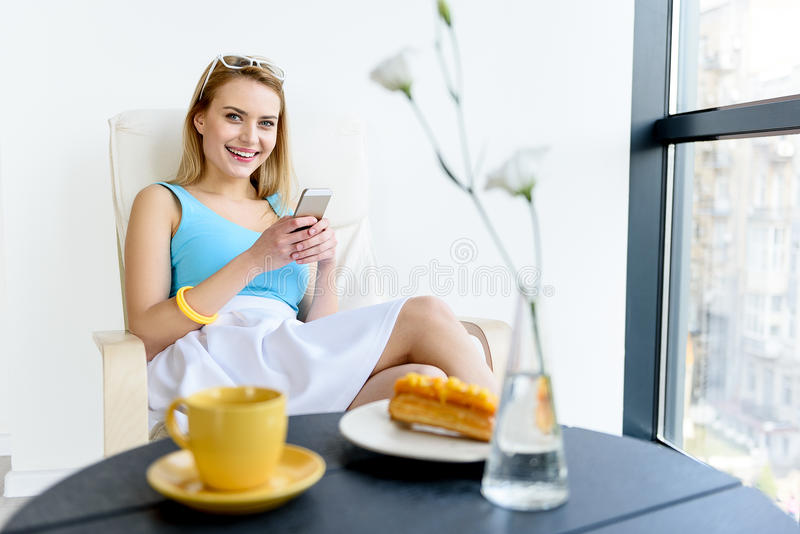 Mensagens felizes da escrita da jovem mulher pelo telefone fotografia de stock royalty free