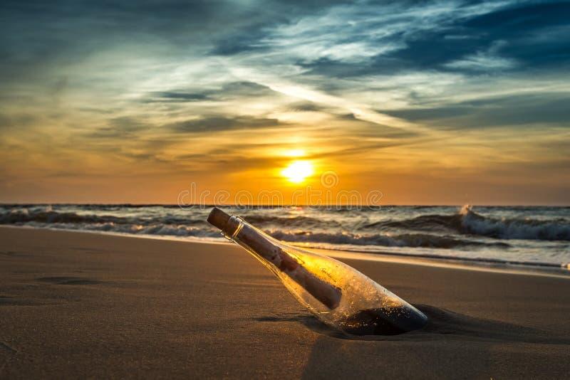 Mensaje antiguo en una botella en una orilla de mar fotos de archivo libres de regalías