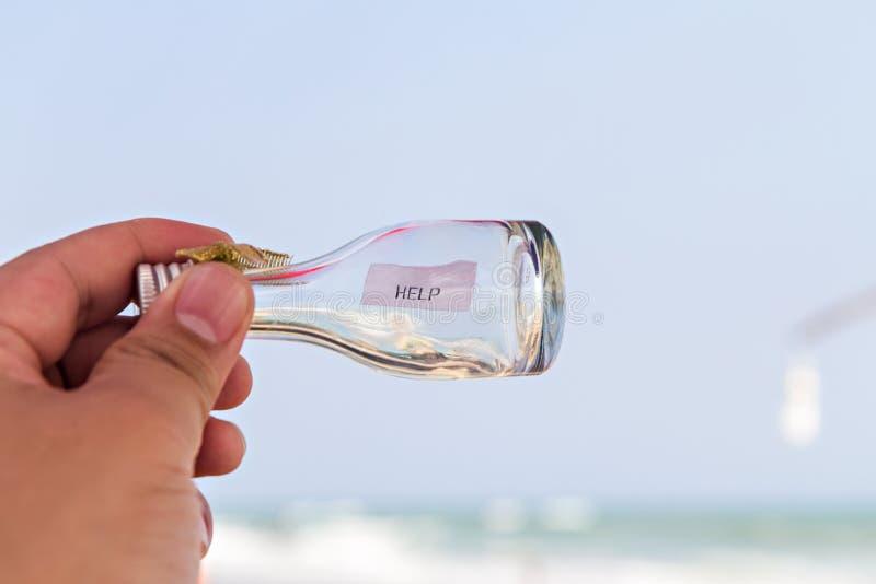 Mensaje de la AYUDA en la botella de cristal foto de archivo libre de regalías