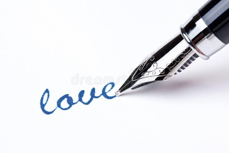 Mensaje de la escritura con la pluma: amor fotografía de archivo libre de regalías