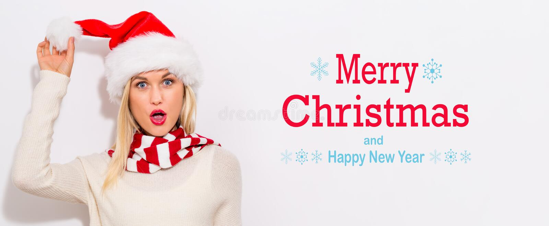 Mensaje de la Feliz Navidad y de la Feliz Año Nuevo con la mujer con el sombrero de Papá Noel foto de archivo