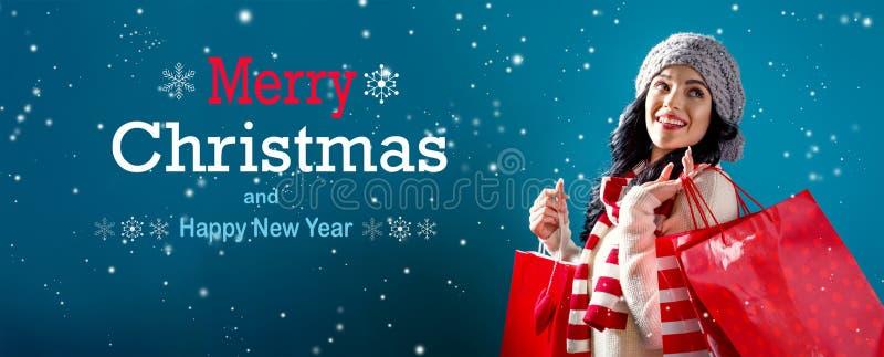 Mensaje de la Feliz Navidad y de la Feliz Año Nuevo con la mujer que sostiene bolsos de compras imagenes de archivo