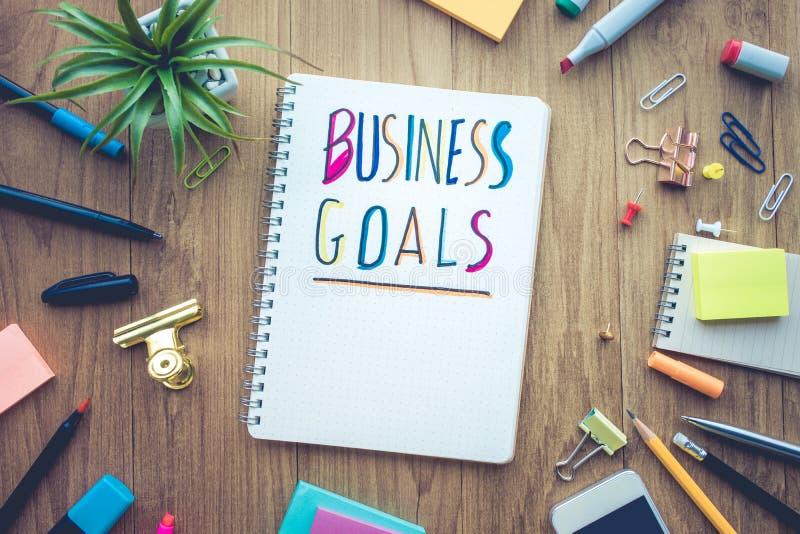Mensaje de las metas de negocio con el documento de la libreta sobre la tabla del escritorio de oficina imagen de archivo libre de regalías