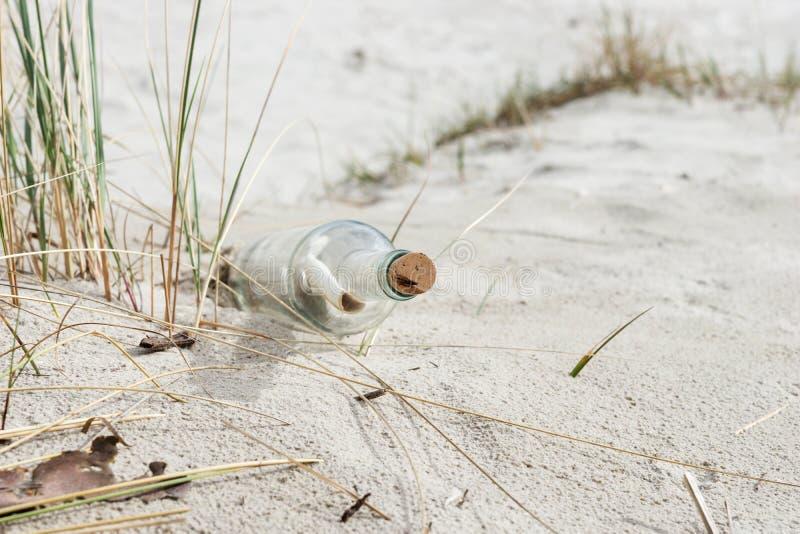 Mensaje de papel en una botella de cristal con un corcho en la arena imágenes de archivo libres de regalías