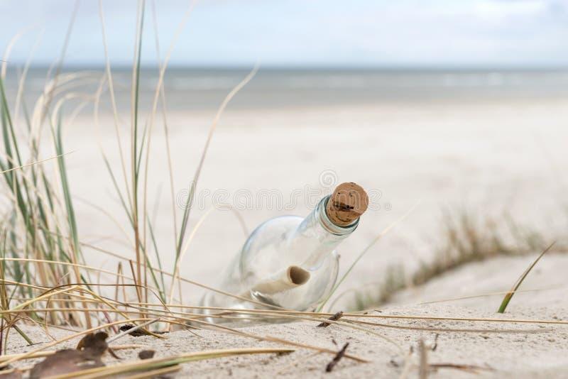 Mensaje de papel en una botella de cristal con un corcho en la arena foto de archivo libre de regalías