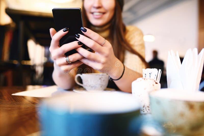 Mensaje de texto de la mujer que mecanografía en el teléfono elegante en un café Imagen cosechada de la mujer joven que se sienta foto de archivo