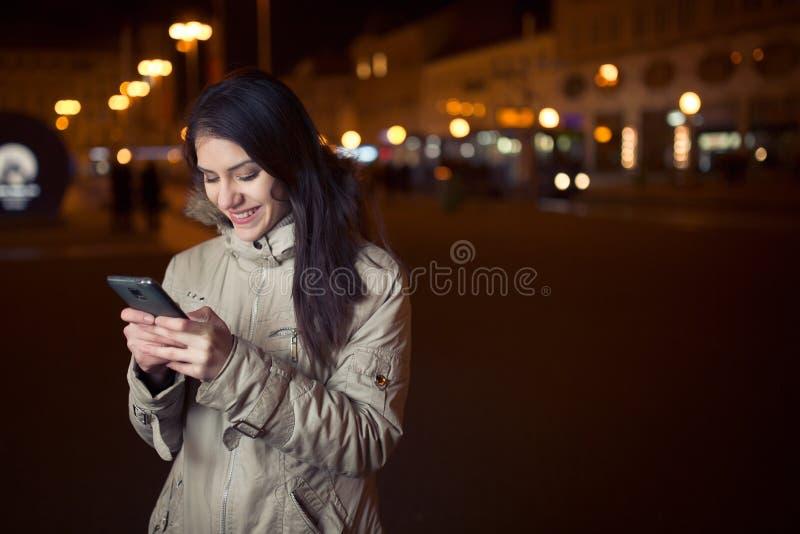 Mensaje de texto de la mujer que mecanografía feliz en un teléfono elegante en una calle de la ciudad mientras que espera Mujer e imagen de archivo libre de regalías