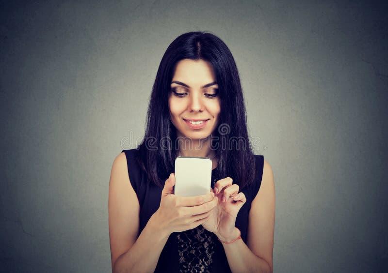 Mensaje de texto de la mujer que mecanografía joven en el teléfono elegante que tiene una conversación agradable fotos de archivo