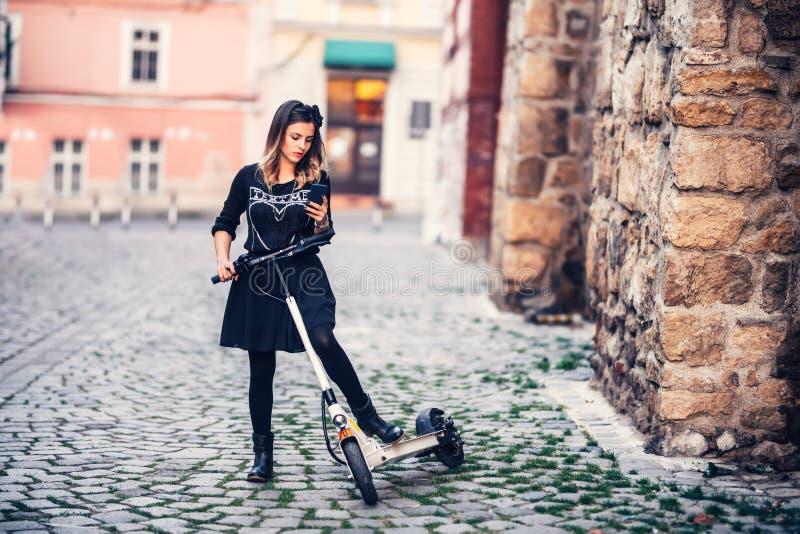 Mensaje de texto hermoso de la escritura de la mujer mientras que monta la vespa eléctrica en las calles urbanas imágenes de archivo libres de regalías