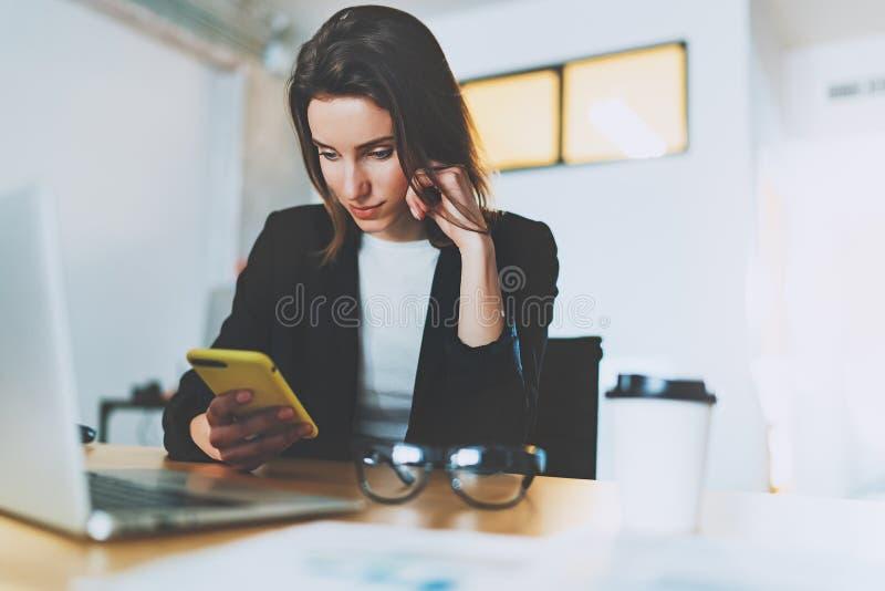 Mensaje de texto de la empresaria que mecanografía atractiva en smartphone mientras que trabaja en la oficina Fondo enmascarado foto de archivo