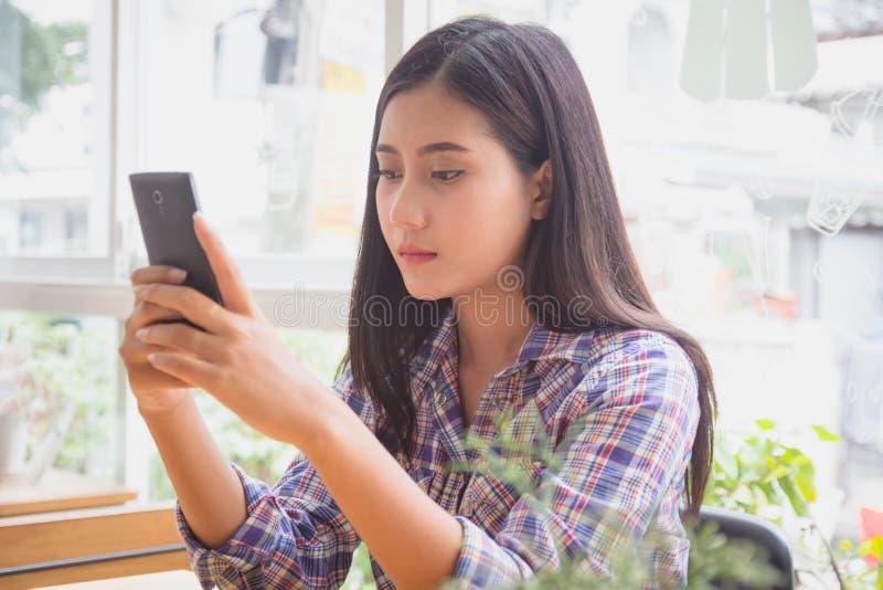 Mensaje de texto de la mujer que mecanografía joven en el teléfono elegante en café moderno Muchacha asiática que se sienta en la imagen de archivo