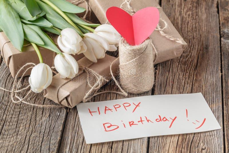 Mensaje del feliz cumpleaños con las flores en la tabla rústica con las flores imágenes de archivo libres de regalías
