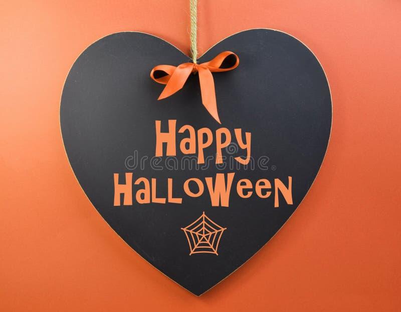 Mensaje del feliz Halloween escrito en la pizarra de la forma del corazón imagenes de archivo