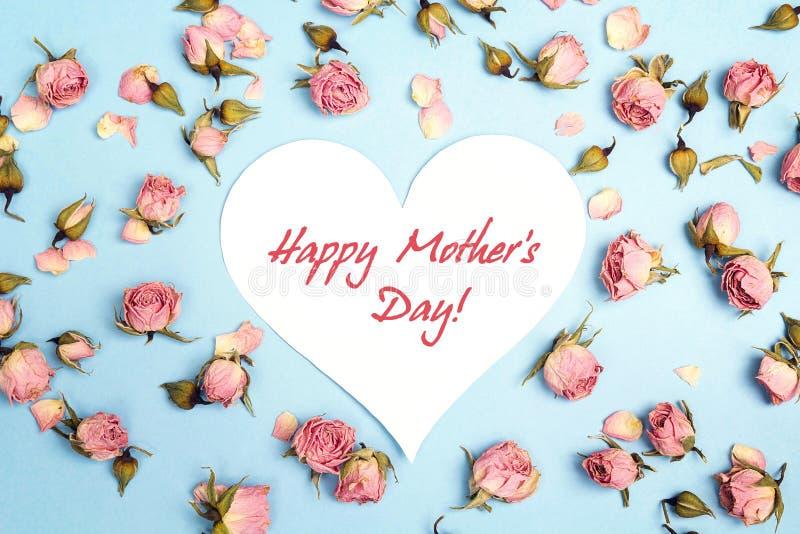 Mensaje del saludo del día de madres con las pequeñas rosas rosadas en backg azul fotografía de archivo