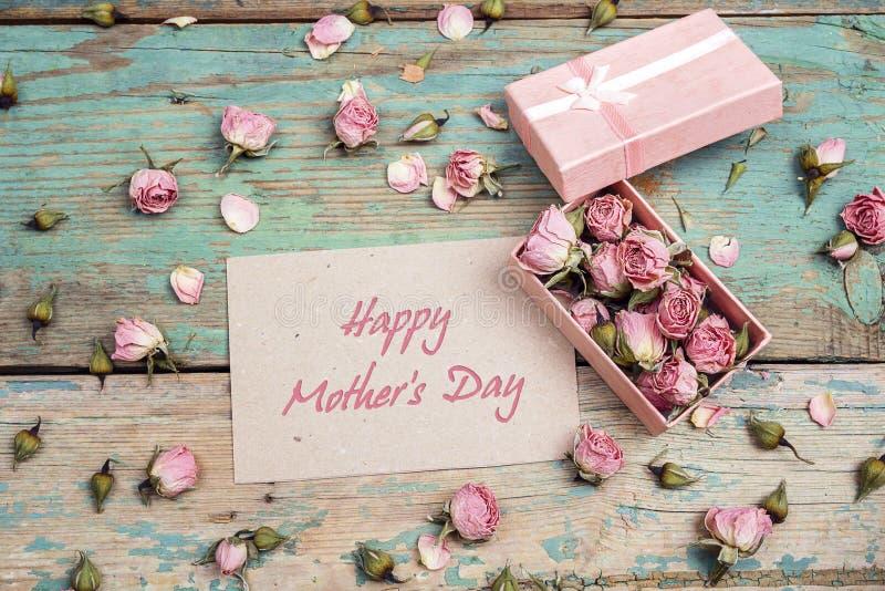 Mensaje del saludo del día de madres con las pequeñas rosas rosadas en una caja encendido foto de archivo