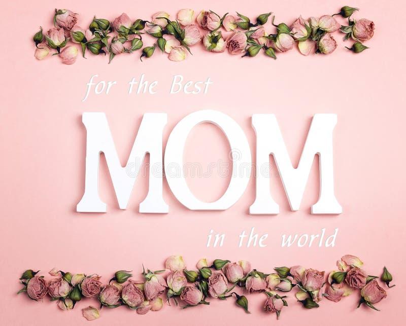 Mensaje del saludo del día de madres con las pequeñas rosas secas en backgr rosado imágenes de archivo libres de regalías